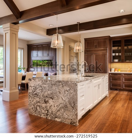 Home Kitchen with Island, Sink, Cabinets, and Hardwood Floors in New Luxury House - stock photo