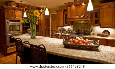 Home Kitchen with Island, Sink, Cabinets, Pendant Lights, Oven, Stove-top Range, and Hardwood Floors in New Luxury House - stock photo