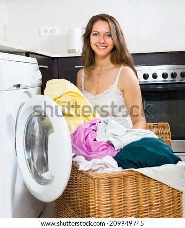 Home laundry. Beautiful long-haired girl using washing machine at home kitchen - stock photo