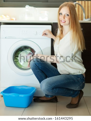 Home laundry. Blonde long-haired woman using washing machine at home