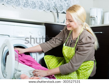 Home laundry. Girl using washing machine at home - stock photo