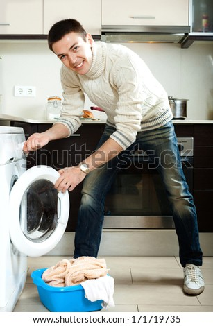 Home laundry. Handsome guy loading clothes into the washing machine  in home