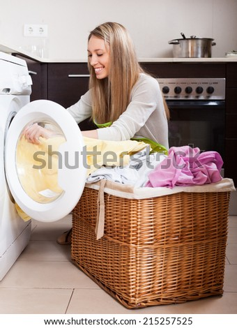 Home laundry. Happy blonde woman loading clothes into washing machine  in home - stock photo