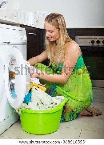 Home laundry. Happy blonde woman working  washing machine  in home kitchen - stock photo
