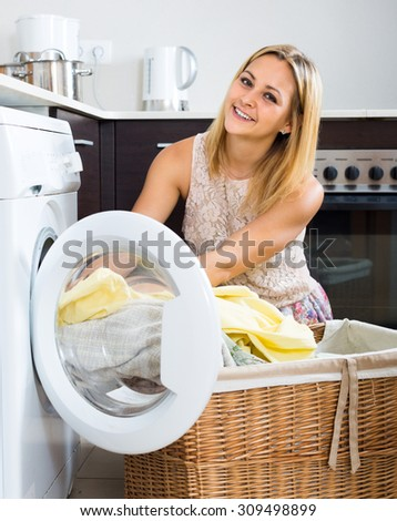Home laundry. Happy girl using washing machine at home - stock photo