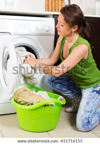 Home laundry. Happy woman loading clothes into washing machine - stock photo