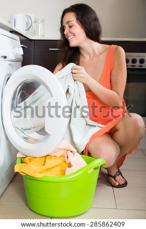 Home laundry. Happy young woman using washing machine at home
