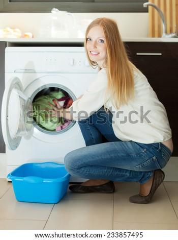 Home laundry. Long-haired woman using washing machine at home