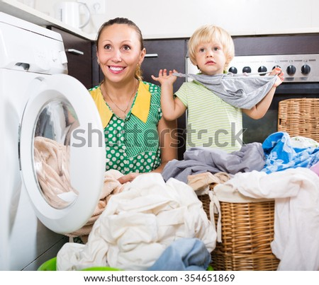 Home laundry. Mother with daughter loading clothes into washing machine in home - stock photo