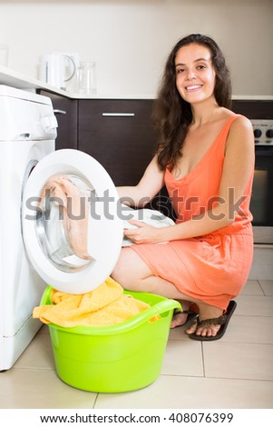 Home laundry. Smiling brunette woman loading clothes into washing machine in home