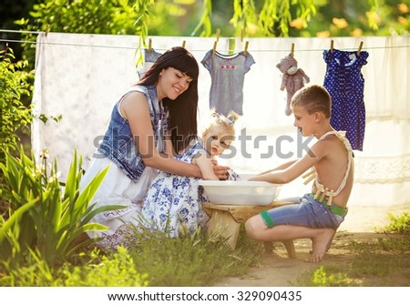 Home laundry. Smiling mother with little children using washing