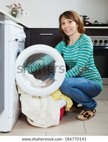Home laundry. Smiling  woman putting clothes in to washing machine  at home