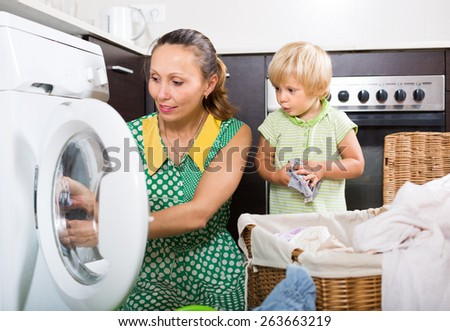 Home laundry. Smiling woman with little child using washing machine at home  - stock photo