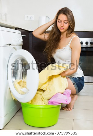 Home laundry. Tired young female with clothes near washing machine at home - stock photo