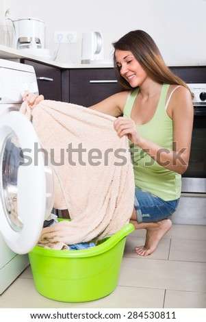 Home laundry. Young woman using washing machine at home