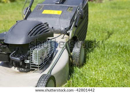Home lawn mower cutting the grass - stock photo