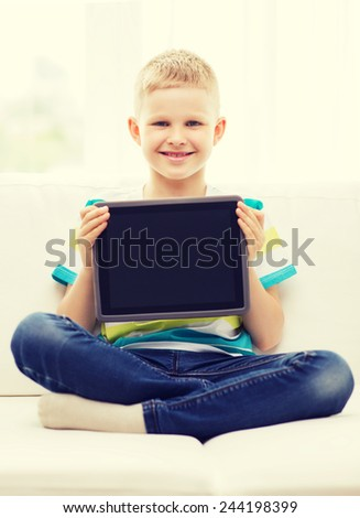 home, leisure, advertising and technology concept - smiling little boy with blank black tablet pc computer screen at home - stock photo