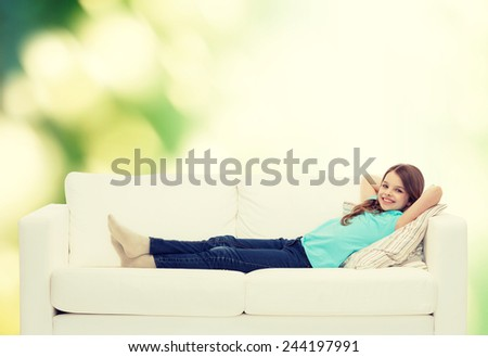 home, leisure and happiness concept - smiling little girl lying on sofa