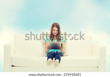 home, leisure, technology and happiness concept - smiling little girl sitting on sofa with tablet pc computer - stock photo