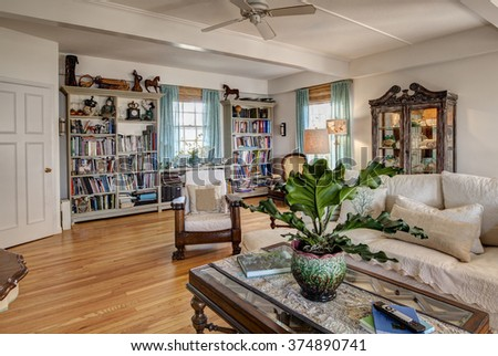 Home library with bookshelves and furniture - stock photo