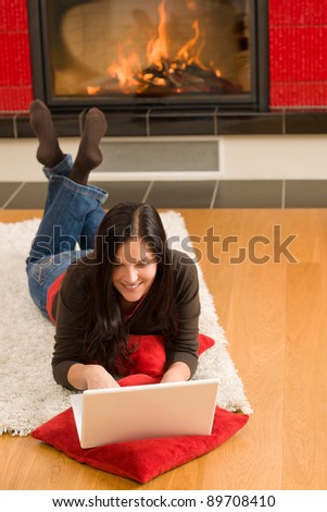 Home living happy young woman by fireplace working on laptop - stock photo