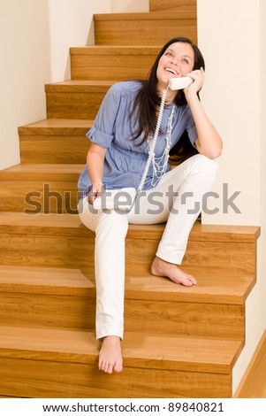 Home living happy young woman calling phone sitting on staircase