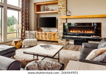 Home living room with hardwood floors, fireplace with roaring fire, coffee table, and mantle in new luxury house - stock photo