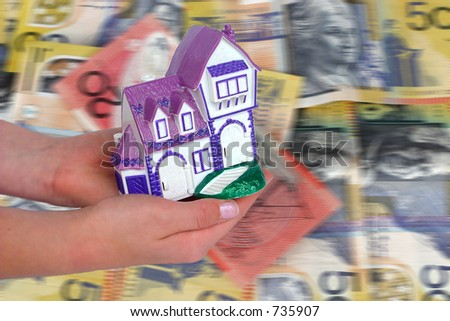home loan, holding a house over australian money background - stock photo