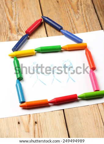 Home, love, family, still life concept. Crayons lying on a paper with children's drawing family. Selective focus, copy space background - stock photo
