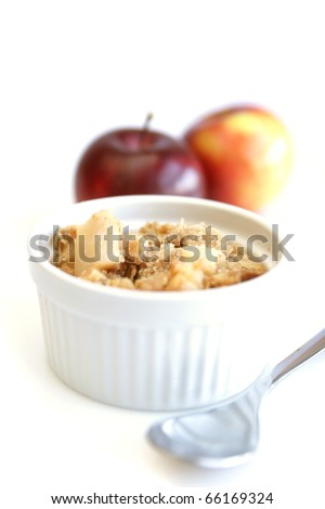 Home made apple crumble in white container with spoon and red apples in background - stock photo