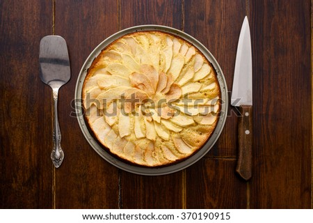Home made apple pie over wooden background with cutlery