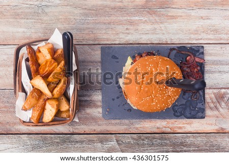 Home made bacon cheese burger with angus beef, tomatoes, onions, cheddar cheese, potato cuts in basket. On slate plate and vintage styled wooden table, top view.