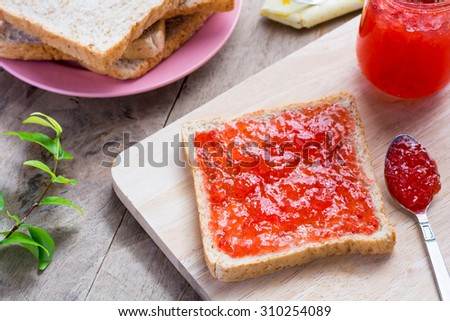 Home made bright red strawberry preserves, spread over a slice of white fresh bread. This can be eaten as shown or combined with another piece of bread and other ingredients to make a sandwich. - stock photo