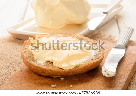 home made butter and half a bun on wooden board - stock photo