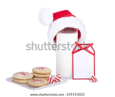 home made candy cane stripped peppermint flavor sugar cookies on a square plate with a glass of milk wearing a santa hat with a card blank for your message - stock photo