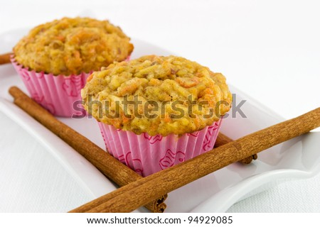 Home made carrot and apple muffins on a white plate with cinnamon sticks. - stock photo