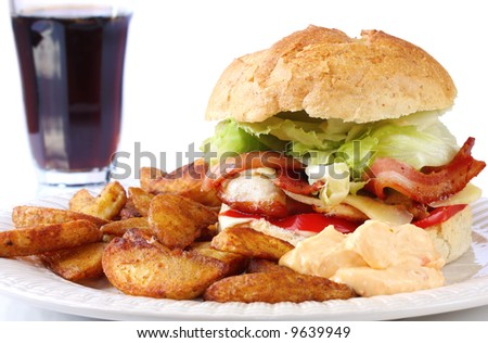 Home-made chicken and bacon burger, served with spicy potato wedges and a sweet chili dipping sauce.  Served on a sourdough bun.  With glass of cola behind. - stock photo