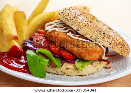 Home made Chicken burger with fried potatoes on old wooden table. - stock photo