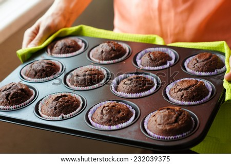 Home made chocolate cupcakes straight from the oven, on a metal tray - stock photo