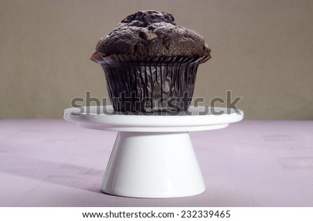 home made double chocolate muffin on a cake stand - stock photo