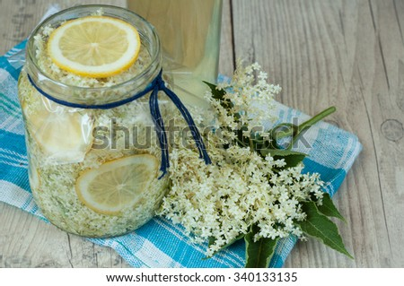 home made elderflower syrup with lemon in the glass - stock photo