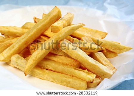 Home-made fat potato chips or french fries, on white paper. - stock photo