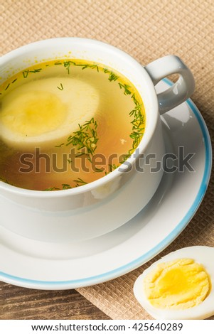 Home-made fresh chicken broth in a soup cup.