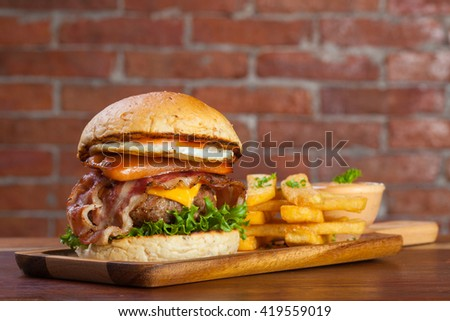 Home made hamburger with bacon and cheese on brick background - stock photo