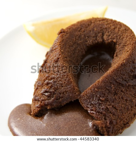 home made hot chocolate fondant with lemon wedge on white saucer - stock photo