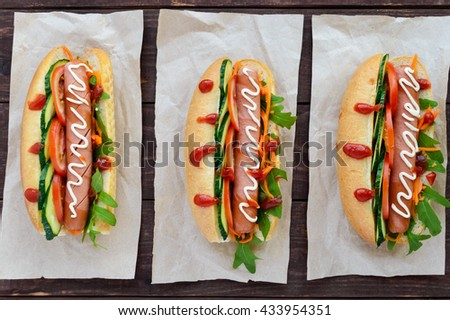 Home made hot dogs with vegetables, juicy sausage and arugula on the wooden background. The top view - stock photo
