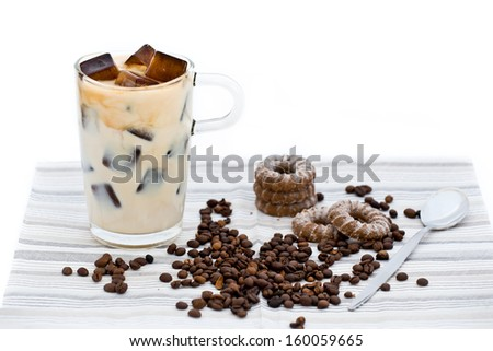 Home-made milky ice coffee with coffee beans and biscuits - stock photo