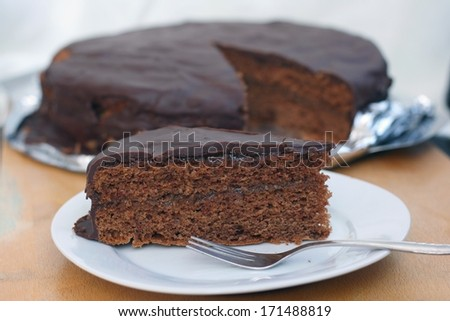Home made piece of sacher chocolate cake, cocoa biscuit with marmalade filling and dark chocolate icing served on a plate, shallow DOF - stock photo