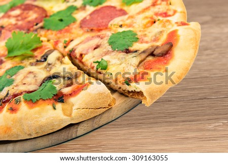 Home made pizza on board at wooden table - stock photo