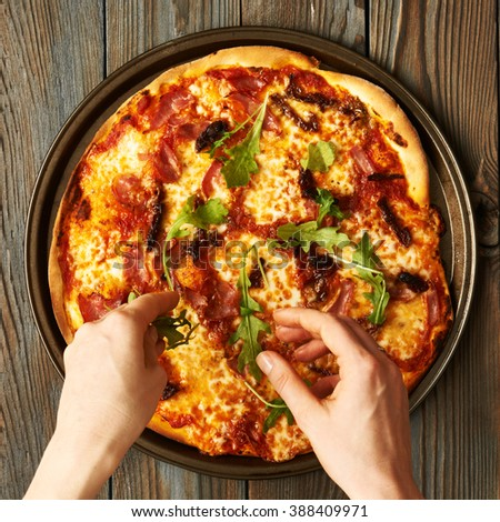 Home made pizza on wooden rustic table - stock photo